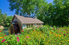 Water mill and flowers Royalty Free Stock Photography