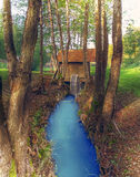 Water Mill in the forest with beautiful blue river Royalty Free Stock Images