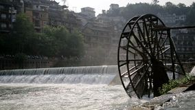 Water Mill Wheel. Handheld shot of water mill wheel on river on sunny day in Fenghuang Ancient Town, Guanxi County, China. Sustainable energy and water power stock footage