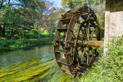 Water mill wheel on river on sunny day. Sustainable energy and water power traditional machinery Stock Images