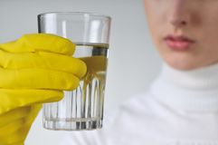 Water - most valuable thing on earth. Young woman in yellow hygienic gloves holding glass of water - concentration stock images