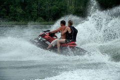 Water motorcycle drivers. Two people driving by water motorcycle Stock Images