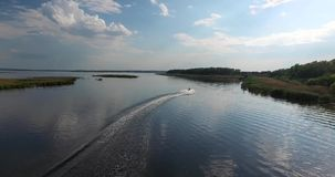 Water motorcycle picks up speed on the river. Top view. Jet ski, with two passengers, up to speed on the river, make a turn, clean river with the shore of the stock footage