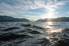 Water of mountain lake. View on the mountains in sunlight from the water surface of mountain lake royalty free stock photos