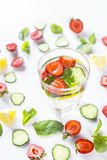Water with natural additives in the bottle. A glass of water with the addition of strawberries, cucumber, mint and lemon. In a circle of bright ingredients on a Stock Photo