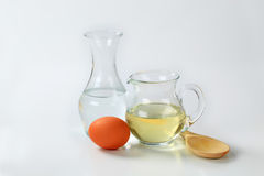 Water, oil, egg and wooden spoon Royalty Free Stock Photography