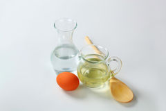 Water, oil, egg and wooden spoon Royalty Free Stock Images