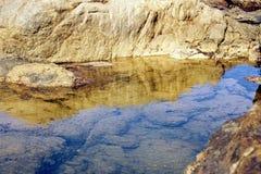 Water onder de rotsen at low tide wordt opgesloten die stock afbeeldingen