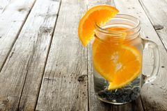 Water with oranges and blueberries against wood Royalty Free Stock Photos