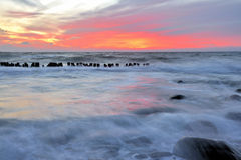 Water over coastal rocks sunset. Glowing sunset and waves of water flowing over coastal rocks Royalty Free Stock Image