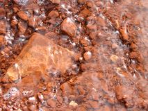 Water over red rocks Stock Images