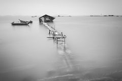 Water overflow on a broken wooden bridge in black and white Stock Image