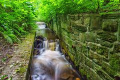 Water Overflow of a lock under a canopy of leaves.  royalty free stock photos