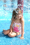 Water park. Little girl ducks under a water sprinkler at a water park Royalty Free Stock Photos