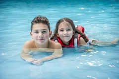 In the water park boy and girl lie in the pool royalty free stock photo