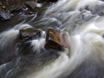 Water passing rocks. A long exposure of water passing rocks in a river stock photo