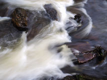 Water passing rocks. A long exposure of water passing rocks in a river Royalty Free Stock Photos