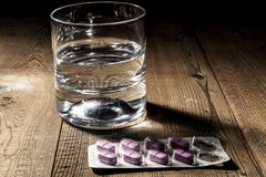 Water and Pills. Whater and pills on table with shadow Royalty Free Stock Images