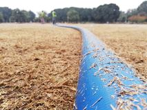 Blue Water pipe with dry grass stock image