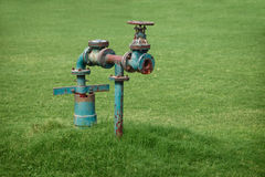 Water pipe on green grass meadow Royalty Free Stock Photos