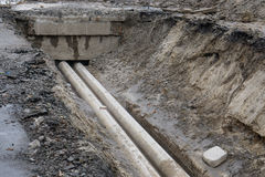 Water pipes in ground during plumbing construction site pit trench ditch Stock Image