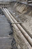 Water pipes in ground during plumbing construction site pit trench ditch Royalty Free Stock Photography