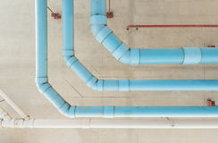 Water pipes hanging on cement ceiling of building Stock Photography
