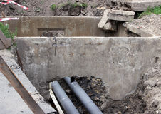 water pipes, insulated roofing sheets during repair in a ditch filled with muddy liquid Stock Photography
