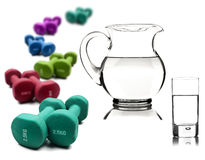 Water in a pitcher and glass with dumbbells Stock Images