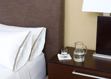 Water pitcher and glass on night stand. In a bedroom Stock Image