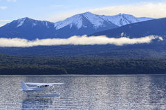 Water plane floating over fresh water lake against beautiful mou Stock Image