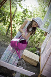 Water the plants. My sweet home. Little girl in front of her wood house for playtime, water the plants stock photo