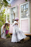Water the plants. My sweet home. Little girls in front of her wood house for playtime in the garden stock photos