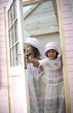 Water the plants. My sweet home. Little girls opening the door of her wood house for playtime royalty free stock image