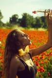 Water in plastic fles bij meisje op gebied van papaver royalty-vrije stock afbeelding