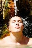 Water pleasure. Portrait of young man under stream of water taking pleasure Stock Image
