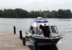 A water police boat is moored at the pier. Stock Image