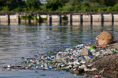 Water pollution. Heavily polluted river inlet with various garbage along shore and floating on water. Manila, Philippines Royalty Free Stock Photo