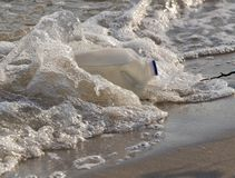 Water Pollution. Gallon milk container washed up on shore at the beach in polluted water Royalty Free Stock Photography