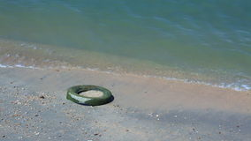 Water pollution - Car tire on beach; stock footage