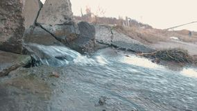 Water pollution discharge from the drain. Side view. stock video footage