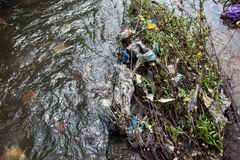 Water pollution. Garbage in the urban stream Royalty Free Stock Photos