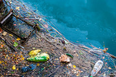 Water pollution old garbage and oil patches on water surface. Water pollution old garbage and oil patches on river surface Royalty Free Stock Photos