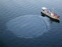 Water pollution from a person by boat Royalty Free Stock Images