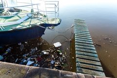 Water pollution. Plastic bottles, packages, trash in river near yacht stock image