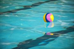 A water polo ball floating on the water in a pool royalty free stock photography