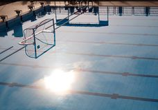 Water Polo goal net in pool with morning sunshine. A photograph showing an Olympic size swimming pool fitted with the waterpolo game goal posts and net.  Taken Royalty Free Stock Photography
