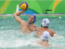 Water Polo Team Hungary in blue  and Team Greece in action during Rio 2016 Olympics Men`s Preliminary Round Group A match Royalty Free Stock Photo