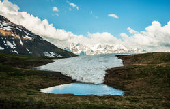 Water pond on the top of the mountain, view on the snowy mountain range. Royalty Free Stock Photography