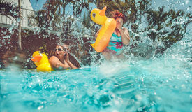 Water pool. Beautiful young fat women is jumping splash into the summer water pool with yellow duck lifebuo Stock Photography